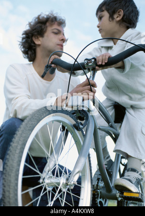 Boy on bicycle looking at father holding onto bicycle, low angle view - Stock Photo