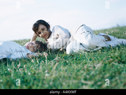 Boy and girl lying on grass - Stock Photo