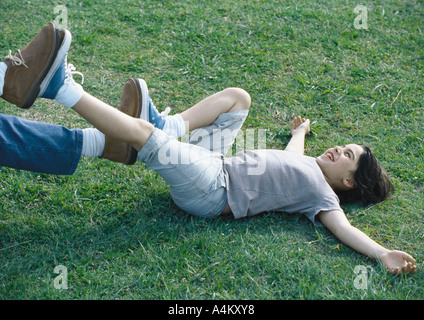 Boy lying on back on grass with feet pushing against man's feet - Stock Photo