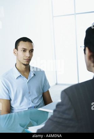 Man in short sleeves with serious expression sitting across table from man in suit - Stock Photo