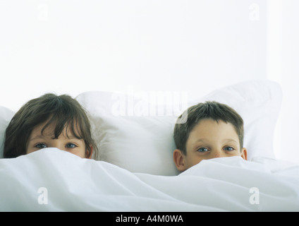 Boy and girl lying in bed, faces partially covered by duvet - Stock Photo