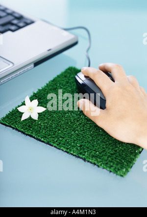 Hand using mouse on mouse pad made of artificial turf - Stock Photo