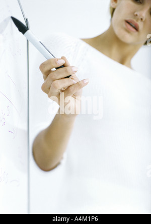 Woman pointing to board with pen, partial view - Stock Photo