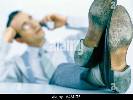 Man talking on phone with feet up on table, focus on feet in foreground - Stock Photo