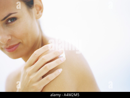 Woman applying sunscreen to shoulder, partial view - Stock Photo