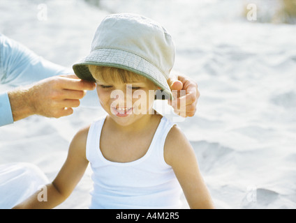 Father's hands putting hat on little boy, on beach - Stock Photo