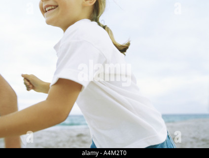 Little girl running on beach - Stock Photo