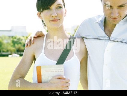 Young couple, man's arm around woman's shoulder - Stock Photo