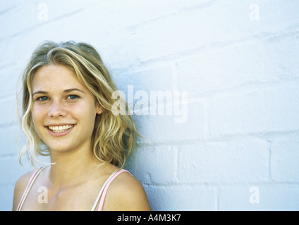 Teenage girl leaning against brick wall, looking at camera, portrait - Stock Photo
