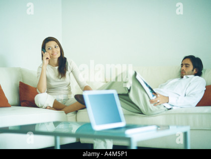 Young couple sitting on couch, man reading while woman uses cell phone - Stock Photo