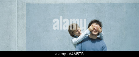 Young woman covering young man's eyes - Stock Photo