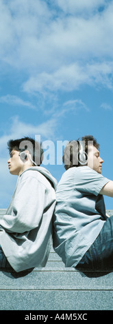 Two young men wearing headphones, sitting back to back - Stock Photo