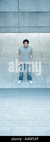 Young man standing at bottom of steps - Stock Photo