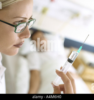 Syringe being held up in front of patient - Stock Photo