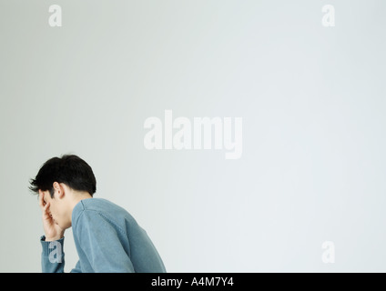 Young man covering face with hand - Stock Photo