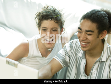Young couple looking at laptop, smiling - Stock Photo