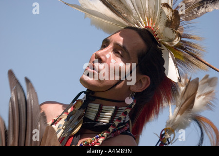 A handsome native American wearing full regalia - Stock Photo