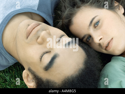 Young couple lying on grass together, close-up - Stock Photo