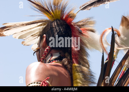 Native American dancer wearing traditional feathered headdress - Stock Photo