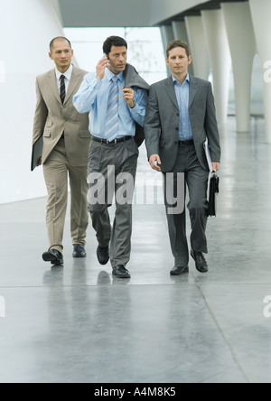 Three businessmen walking through lobby, one using cell phone - Stock Photo