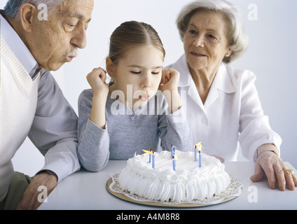 Girl sitting with grandparents, blowing out candles on cake
