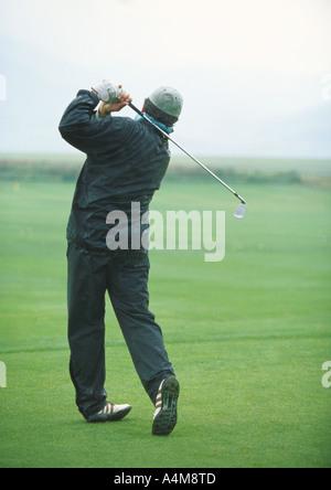 Golfer swinging - Stock Photo