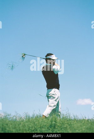Golfer swinging - Stock Photo