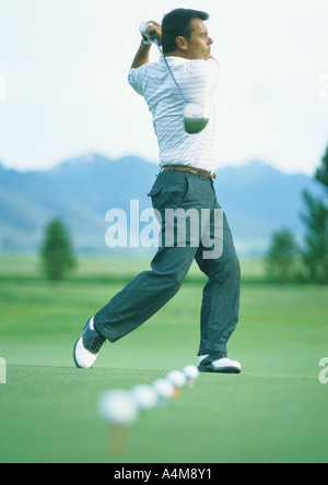 Golfer practicing on driving range - Stock Photo
