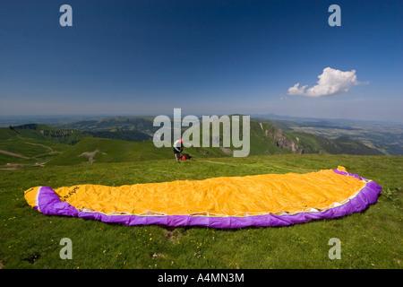 A paraglider preparing his takeoff over the Sancy Massif (France). Parapentiste préparant son envol dans le massif - Stock Photo