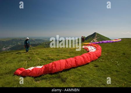 Paragliders preparing their takeoffs (Puy de Dôme - France). Parapentistes préparant leur envol (Puy de Dôme - France). - Stock Photo