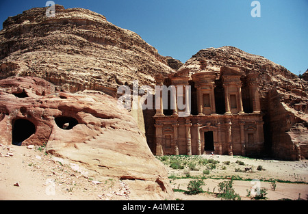 The Monastery Al Deir at the ancient rose red city of Petra Jordan Nabatean rock carved tomb in the foreground also - Stock Photo