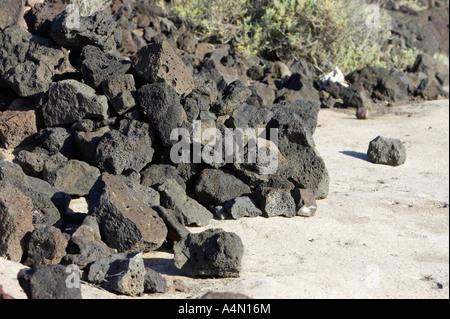 pile of rocky volcanic lava rock boulders on the beach coastline at punta de teno Tenerife Canary Islands Spain - Stock Photo