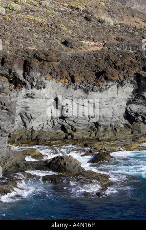 vertical man walking along rocky volcanic lava rock cliff formations on the coast at punta de teno Tenerife Canary - Stock Photo