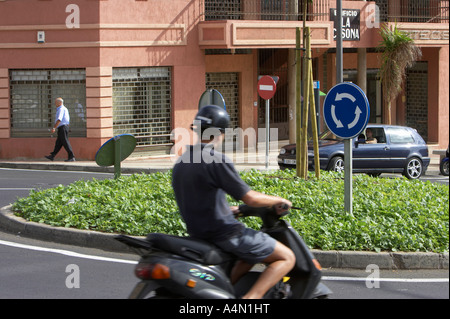 hispanic youth wearing helmet enters roundabout on scooter moped in La Cuesta Tenerife Canary Islands Spain - Stock Photo