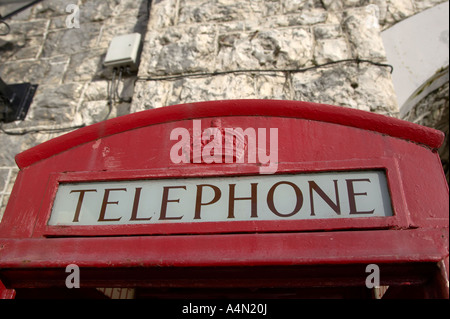 top of old style red telephone box with crown detail in Carnlough county antrim white limestone bridge in the background - Stock Photo