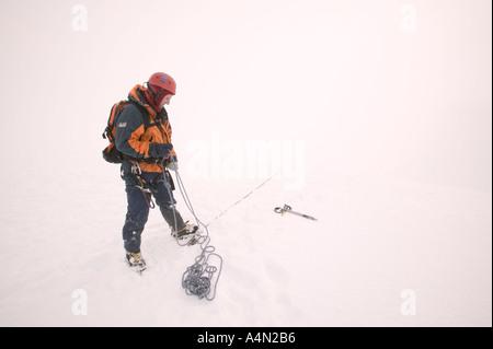 winter climber belays partner climbing on aonach Mhor Scotland - Stock Photo