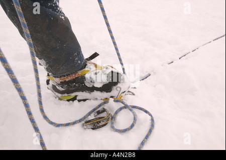 winter climber belays partner on an climb on aonach Mhor - Stock Photo