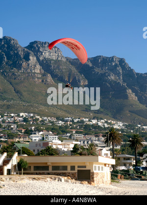A tandem paraglider about to land on Camps Bay beach in Cape Town. - Stock Photo