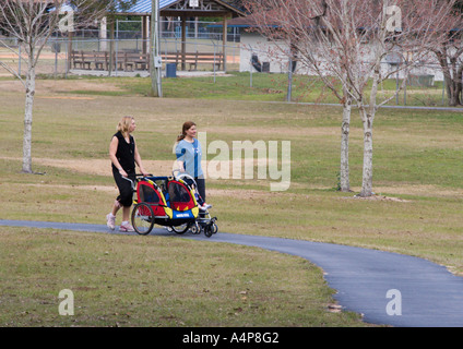 Two women walking and pushing babies in strollers through Jervey Gannt Park in Ocala Florida USA - Stock Photo