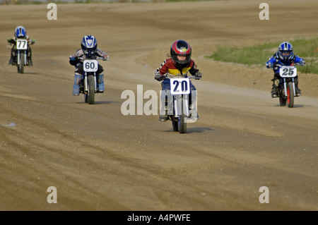 Young girl with 20 bike leads a pack of 4 racers during dirt track motorcycle race Croswell Michigan USA - Stock Photo