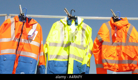 Three high visibility jackets hung on a line - Stock Photo