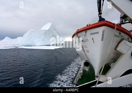 Tourist ship passing a large iceberg in the Weddell Sea in Antarctica - Stock Photo