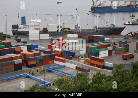 Container ship and dockside full of shipping containers in a busy container port - Valparaiso in Chile - Stock Photo