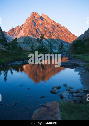 Mount Stuart reflected in still water at sunset Central Cascades Washington USA - Stock Photo