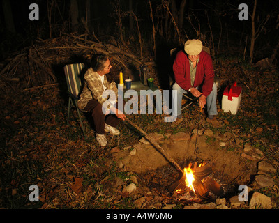 Couple Cooking over Campfire - Stock Photo