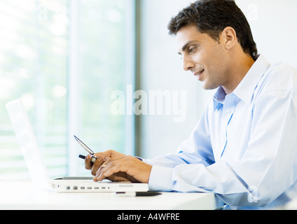 Businessman using cell phone and laptop - Stock Photo
