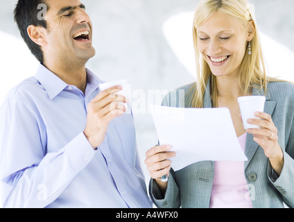 Businessman and businesswoman holding cups and laughing over document - Stock Photo