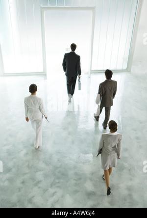 Four executives walking across lobby toward exit - Stock Photo