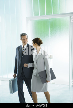 Businessman and businesswoman walking through lobby - Stock Photo