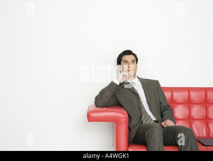 Businessman sitting on couch - Stock Photo